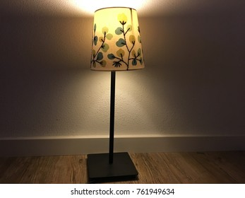 Lamp with lampshade shining in a dimly lit room