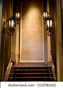 A lamp lit stair case as a hallway inside a hotel leading to the next floor.