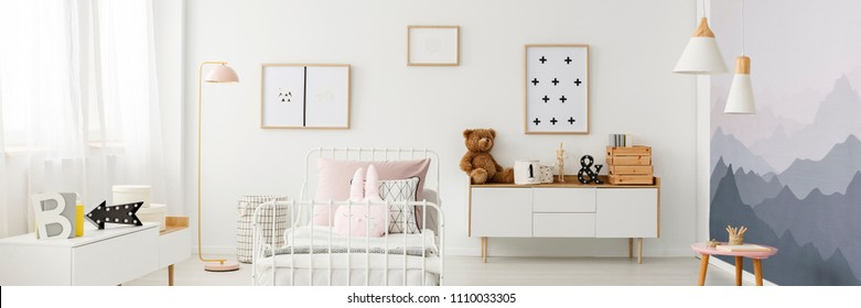 Lamp next to white, metal bed against the wall with posters in girl's bedroom interior with cupboard