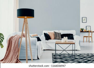 Lamp next to white sofa with pink blanket in open space interior with carpet and table. Real photo