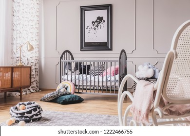 Lamp on cabinet and armchair in grey kid's bedroom interior with poster above cradle. Real photo