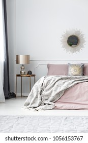 Lamp on gold table next to pink bed with grey blanket against the wall with mirror in bedroom interior