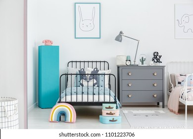 Lamp on grey cabinet next to black bed and blue pedestal in siblings bedroom interior. Real photo