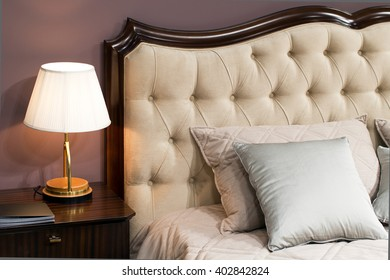 Lamp on a night table next to upholstery bed with pillows