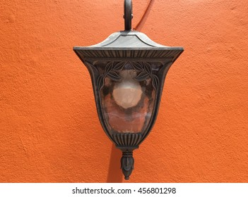 Lamp on red wallpaper.