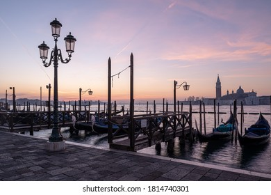 A lamp on the Riva degli Schiavoni waterfront with docked gondolas and San Giorgio Maggiore basilica in the background during a sunsrise in Venice, Italy