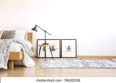 Lamp on stool next to bed in bright bedroom with copy space on white wall and posters on the floor