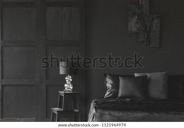 Lamp on stool next to bed in dark black bedroom interior with wooden wall. Real photo