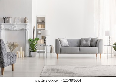 Lamp on table next to grey settee in white loft interior with armchair and copy space. Real photo