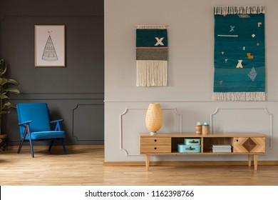 Lamp on wooden cupboard in living room interior with blue armchair under poster. Real photo