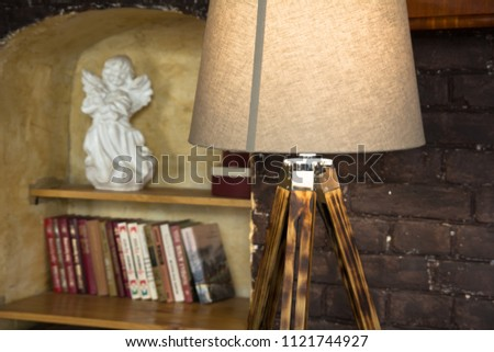 Lamp On Wooden Legs And Bookshelf With Porcelain Angel In A Niche