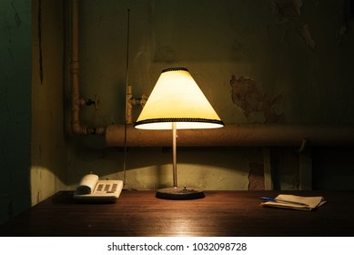 Lamp and phone on a brown wooden desk in old shabby abandoned basement room