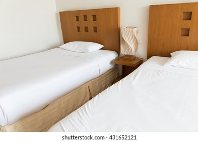 lamp, pillow and white bed in hotel room (selected focus)