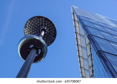 Lamp post in front of a Glass and concrete facade on a modern corporate skycraper building