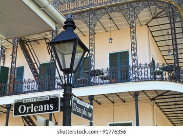 A lamp post and wrought iron balconies at the corner of Orleans and Dauphine streets in the French Quarter of New Orleans