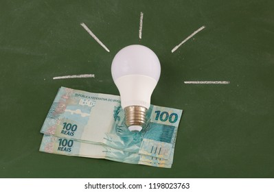 Lamp and real hundred notes with green frame background. Having an idea. Light on. Brazilian money. Brazil.