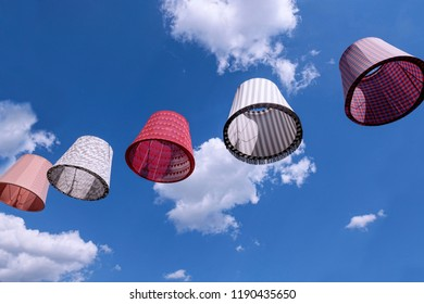 Lamp shades flying over a sky with clouds