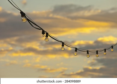 Lamp string hanging against a goldish sky background