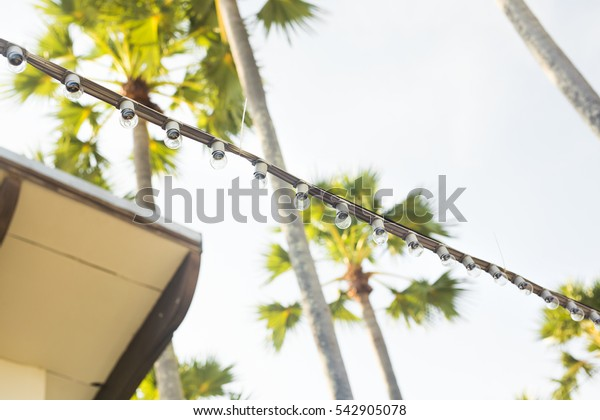 Lamp string hanging outside against ablue sky background