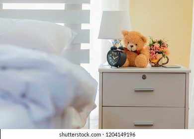 Lamp, Teddy bear, Flower jar, Black alarm clock, Smartphone on bedside table and white pillows on bed in luxury interior bedroom.
