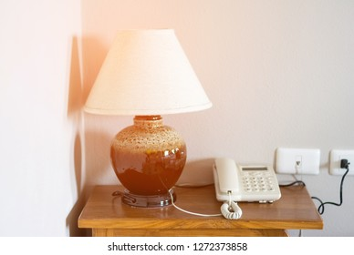 Lamp and telephone on bedside table in bedroom