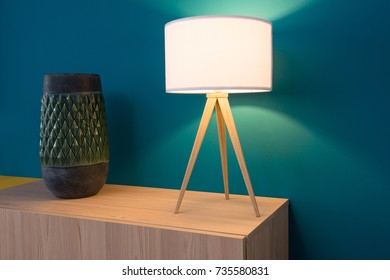 Lamp and vase on cabinet, blue wall in background
