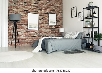 Lamp and white carpet in grey bedroom with bright pillows on bed and posters on red brick wall
