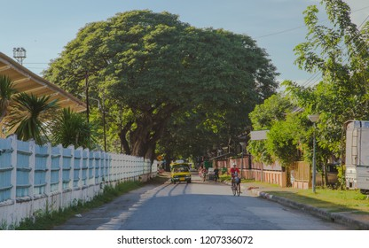 Lampang Thailand - 17 October 2018 At 4:30 PM. Yellow Mini Truck Taxi [Famous Lampang Thailand Passenger Car] and Many Vehicles are Driving Under Shadow of Beautiful Big Trees.