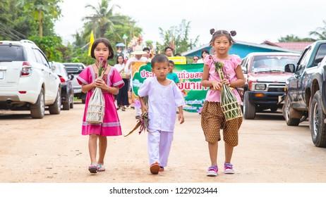 Lampang Thailand- 24 October 2018 At 10:00 AM. Three Children [Two Girls & One Boy] are Holding Kuay Sa-Lak in thier Hands in Tan Kuay Sa-Lak Festival Parade.