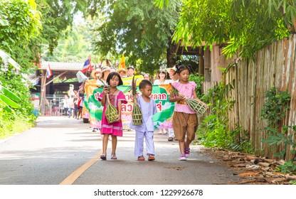 Lampang Thailand- 24 October 2018 At 10:00 AM. Happy Cute Three Children [Two Girls & One Boy] are Holding Kuay Sa-Lak in thier Hands in Tan Kuay Sa-Lak Festival Parade.
