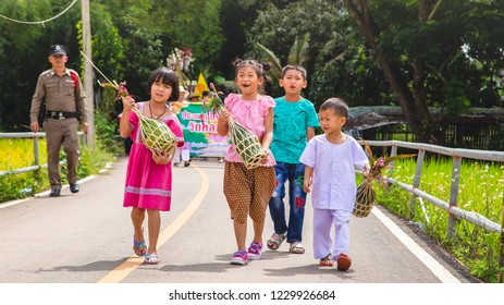 Lampang Thailand- 24 October 2018 At 10:00 AM. Happy Cute Four Children [Two Girls & Two Boys] are Holding Kuay Sa-Lak in thier Hands in Tan Kuay Sa-Lak Festival Parade.