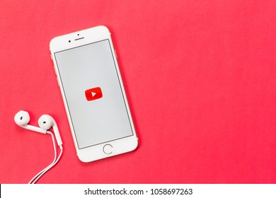 Lampang. Thailand. April 1, 2018. Youtube application working on Apple iPhone 6 with white earphone on red background in top view