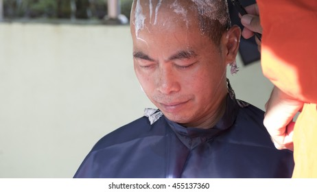 Lampang, Thailand - July 18, 2016: monk shave hair of man who will become buddhism monk in ordination ceremony at Bunyanupab temple in Lampang, Thailand on July 18, 2016.