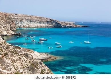 Lampedusa island, Mediterranean Sea, Italy: boats anchored in port behind island