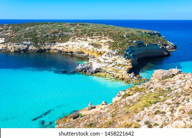 "Lampedusa Island Sicily - Rabbit Beach and Rabbit Island  Lampedusa ""Spiaggia dei Conigli"" with turquoise water and white sand at paradise beach. Mediterranean scrub with thyme and cardoon."