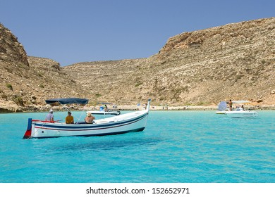LAMPEDUSA, ITALY - JULY 17: Some boats near the beach Spiaggia dei Conigli, the most beautiful beach in the world according Travelers Choice Awards list, on July 17, 2013, in Lampedusa, Italy.