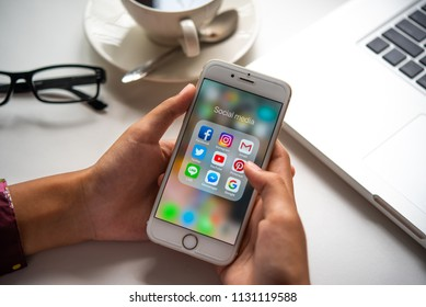 LAMPHUN, THAILAND - JULY 8th, 2018: Hands using Iphone6 gold color with icons of social media on screen with laptop, smartphone life style, smartphone in everyday