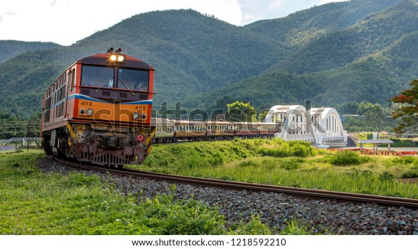 LAMPHUN, THAILAND - MAY 25, 2018: The state railway of Thailand Alstrom locomotive of train no.52 from Chiang Mai to Bangkok passing white bridge (Thachompu) in Lamphun, northern of Thailand