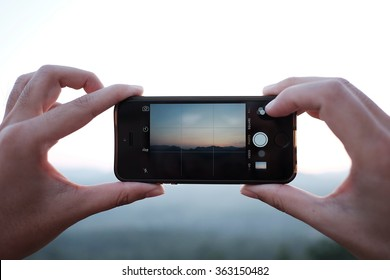 LAMPHUN, THAILAND - October 26, 2015: Hand holding a iPhone 5s displaying the Camera app to capture a mountain and sunset view at Li  district, Lamphun, Thailand.