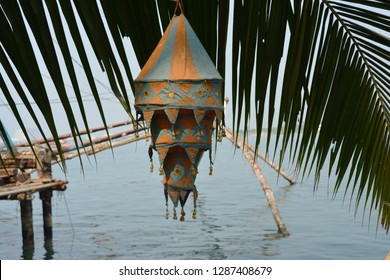 Lampion hanging on a palm tree leaf in the fishing harbor of Fort Kochin, Kerala