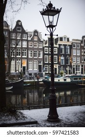 Lamppost and Dutch houses alongside a canal in the winter in Amsterdam  Netherlands .