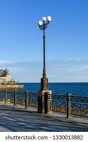 Lamppost on the background of the sea. Embankment of the resort town of Sudak, Crimea. Early sunny evening in September.