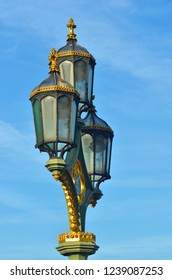 A lamp-post with three glass lanterns is seen against a blue sky with pale white clouds. The lamps have black iron work and gold detailing.
