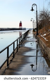 Lampposts reflect on a wet sidewalk with a lighthouse in the distance in Charlevoix, Michigan