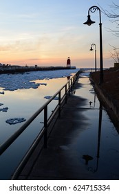 Lampposts reflect on a wet sidewalk at sunset with a lighthouse in the distance.
