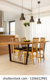 Lamps above wooden table and chairs in minimal bright dining room interior. Real photo