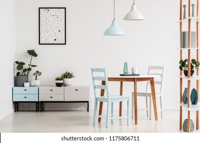 Lamps above wooden table and chairs in white dining room interior with poster above cupboard. Real photo