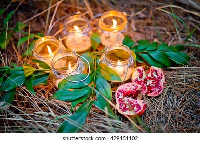 The lamps made of a jars with a candles  is  in the forest. Wedding  lighting decor. Sparks in a garden