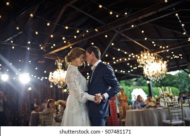 Lamps sparkle behind a wedding couple dancing at the first time
