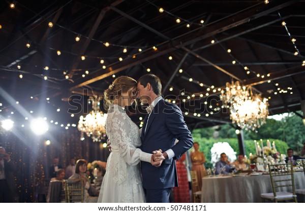 Les lampes brillent derrière un couple de mariés dansant pour la première fois